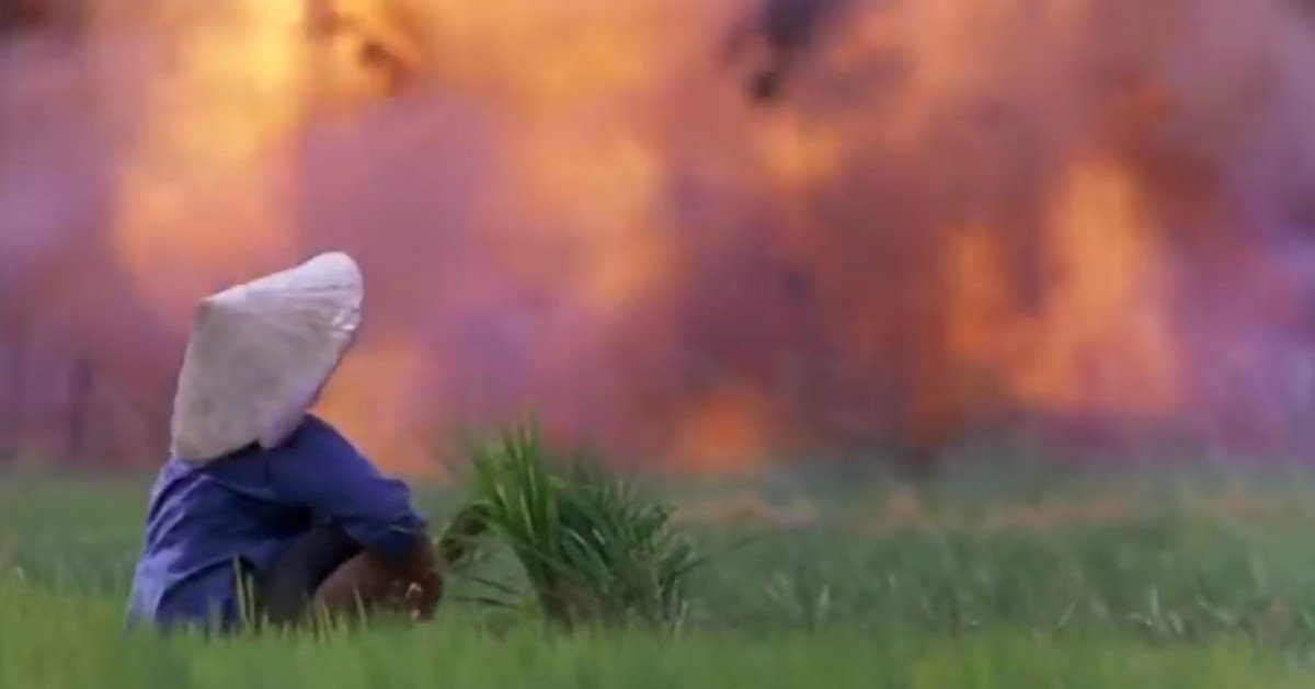 Woman sitting in a field watching a village burn